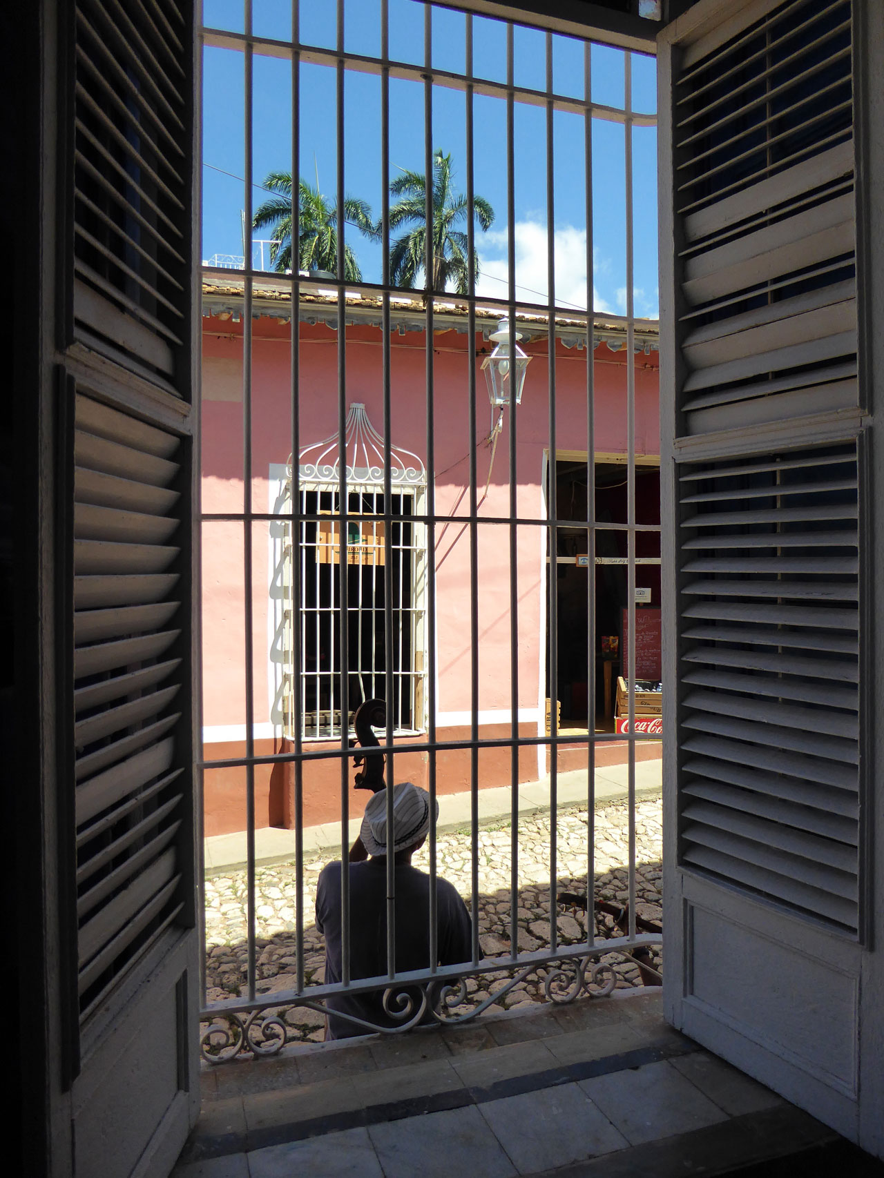 Musician viewed through a cage window in Trinidad, Cuba